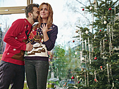 Couple standing in front of Christmas tree, man kissing surprised woman - RHF001329