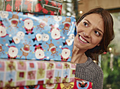 Woman carrying stack of Christmas parcels - RHF001332