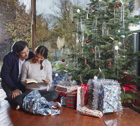 Couple reading book under Christmas tree - RHF001338
