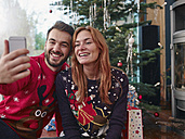 Happy couple taking selfie in front of Christmas tree - RHF001341