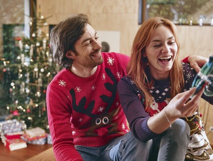 Happy couple unwrapping children's shoes in front of Christmas tree - RHF001347