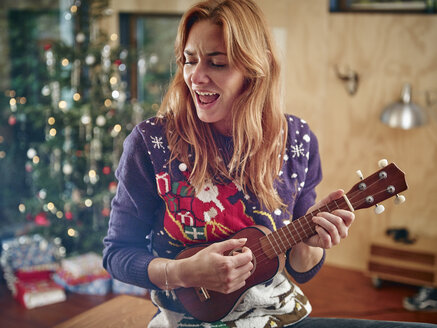 Blond woman playing ukulele in front of Christmas tree - RHF001350