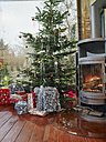 Christmas presents under Christmas tree next to cozy fireplace - RHF001356