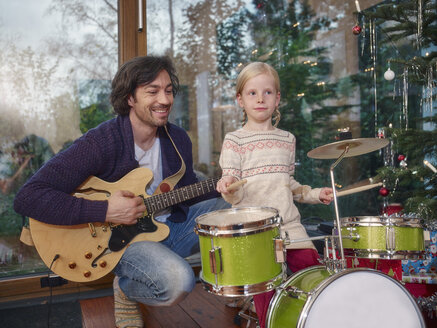 Father and daughter playing music on Christmas Eve - RHF001359