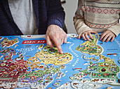 Father and daughter playing with world map jigsaw puzzle - RH001371