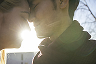 Young couple in love head to head at backlight, close-up - ABZF000255
