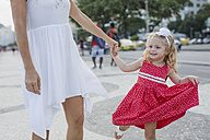 Brasil, Rio de Janeiro, mother and daughter walking hand in hand - MAUF000255