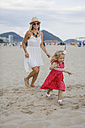 Brasil, Rio de Janeiro, happy mother and daughter running on Copacabana beach - MAUF000261