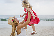 Brasil, Rio de Janeiro, mother lifting up daughter on Copacabana beach - MAUF000264