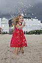 Brasil, Rio de Janeiro, girl playing with sand on Copacabana beach - MAUF000276