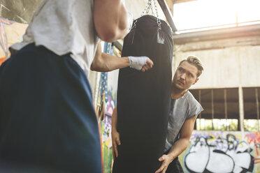 Boxer exercising at punch bag - MADF000842