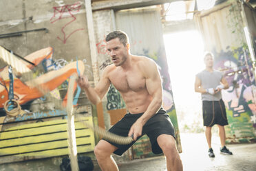 Young man having a workout with ropes - MADF000845
