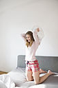 Laughing young woman having pillow fight on bed - FMKF002462