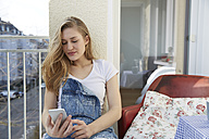 Portrait of young woman sitting on balcony looking at her smartphone - FMKF002465