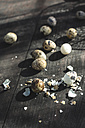 Whole and broken quail eggs on dark wood - DEGF000691