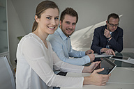 Smiling woman with digital tablet in conference room - PAF001573