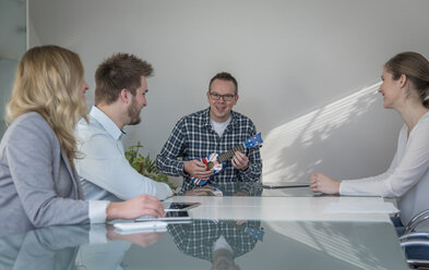 Colleagues having a meeting with man playing banjo - PAF001579