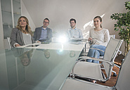 Four colleagues attending a presentation with projector in conference room - PAF001585