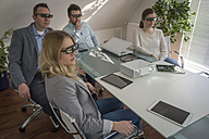 Four colleagues with 3d glasses attending a presentation with projector in conference room - PAF001588