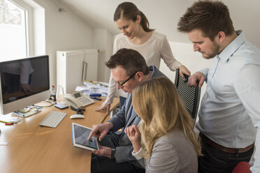 Four colleagues in office sharing digital tablet - PAF001600