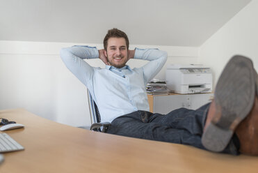Smiling young man in office with feet on desk - PAF001603