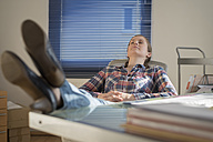 Young woman in office with feet on desk and closed eyes - PAF001615