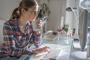 Young woman at desk in office holding cup of coffee - PAF001618