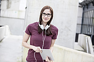 Portrait of smiling young woman with headphones and digital tablet - FMKF002490