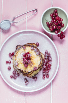 Stack of American pancakes with  red currents sprinkled with icing sugar - SBDF002704