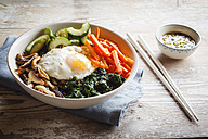 Vegetarian korean rice bowl with mushroom, spinach, cucumber, carrot and fried egg - EVGF002835