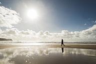 France, Bretagne, Finistere, Crozon peninsula, woman walking on the beach - UUF006702