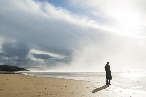 France, Bretagne, Finistere, Crozon peninsula, woman standing on the beach - UUF006711