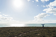 France, Bretagne, Finistere, Crozon peninsula, woman standing at the coast with outstretched arms - UUF006723