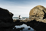 France, Bretagne, Finistere, Crozon peninsula, man walking on rocky beach with surfboard - UUF006729