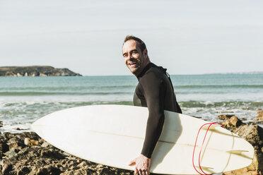 France, Bretagne, Finistere, Crozon peninsula, happy man on rocky beach with surfboard - UUF006732