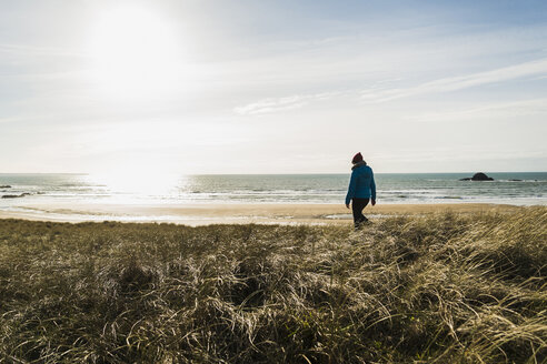 France, Bretagne, Finistere, Crozon peninsula, woman walking at the coast - UUF006735