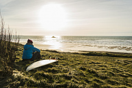 France, Bretagne, Finistere, Crozon peninsula, woman sitting at the coast at sunset with surfboard - UUF006744