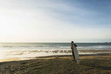 France, Bretagne, Finistere, Crozon peninsula, man standing at the coast with surfboard - UUF006747