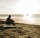 France, Bretagne, Finistere, Crozon peninsula, man sitting at the coast at sunset with surfboard - UUF006750