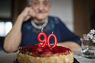 Candles on a birthday cake of a senior woman celebrating her ninetieth birthday - RAEF000929