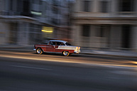 Cuba, Havana, American vintage car driving on a road at twilight - STE000164