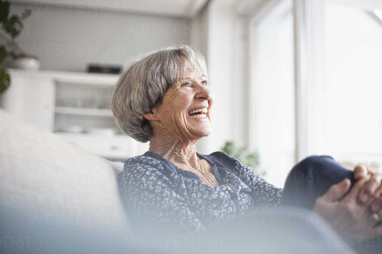 Portrait of laughing senior woman sitting on couch at home - RBF004107 - Rainer Berg/Westend61