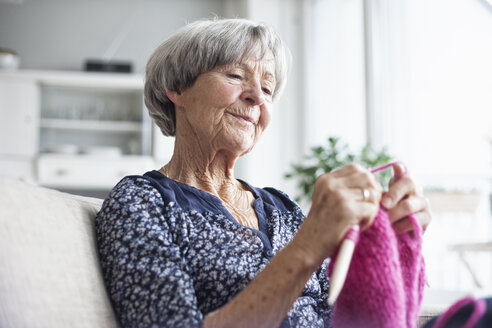 Portrait of knitting senior woman sitting on couch at home - RBF004113