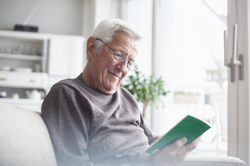 Portrait of senior man sitting on couch at home reading a book - RBF004116