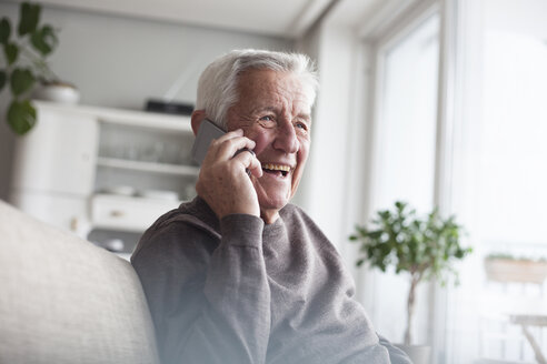 Portrait of laughing senior man telephoning with smartphone at home - RBF004119
