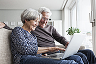 Happy senior couple sitting on the couch in the living room using laptop - RBF004122