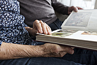 Hands of senior couple holding photo album, close-up - RBF004125