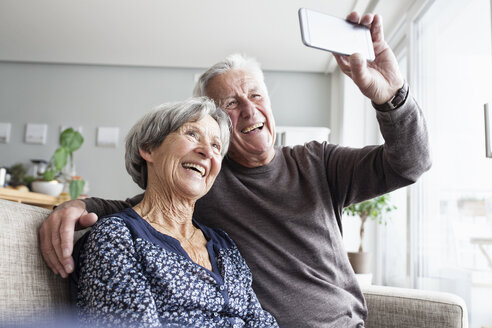 Laughing senior couple sitting on the couch in the living room taking selfie with smartphone - RBF004128