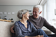 Laughing senior couple sitting together on the couch in the living room - RBF004131