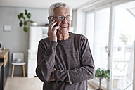 Portrait of smiling senior man telephoning with smartphone at home - RBF004143